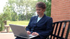 woman sits in a business suit with a laptop on her lap